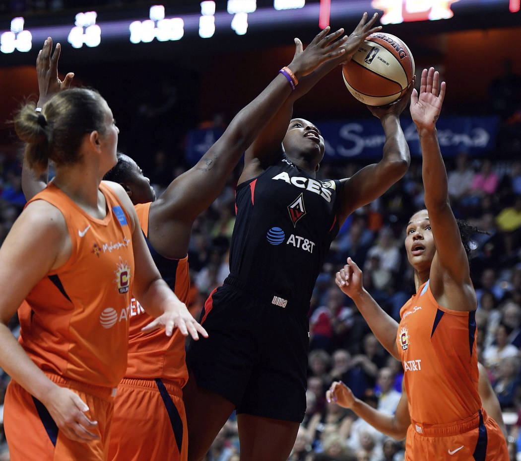 Las Vegas Aces guard Jackie Young scores between Connecticut Sun forwards Shekinna Stricklen, b ...