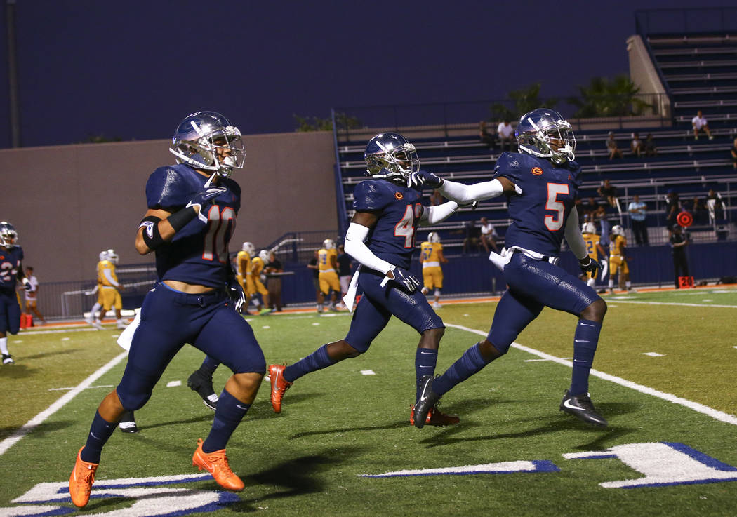Bishop Gorman players celebrate a touchdown by Fabian Ross, not pictured, during the first half ...