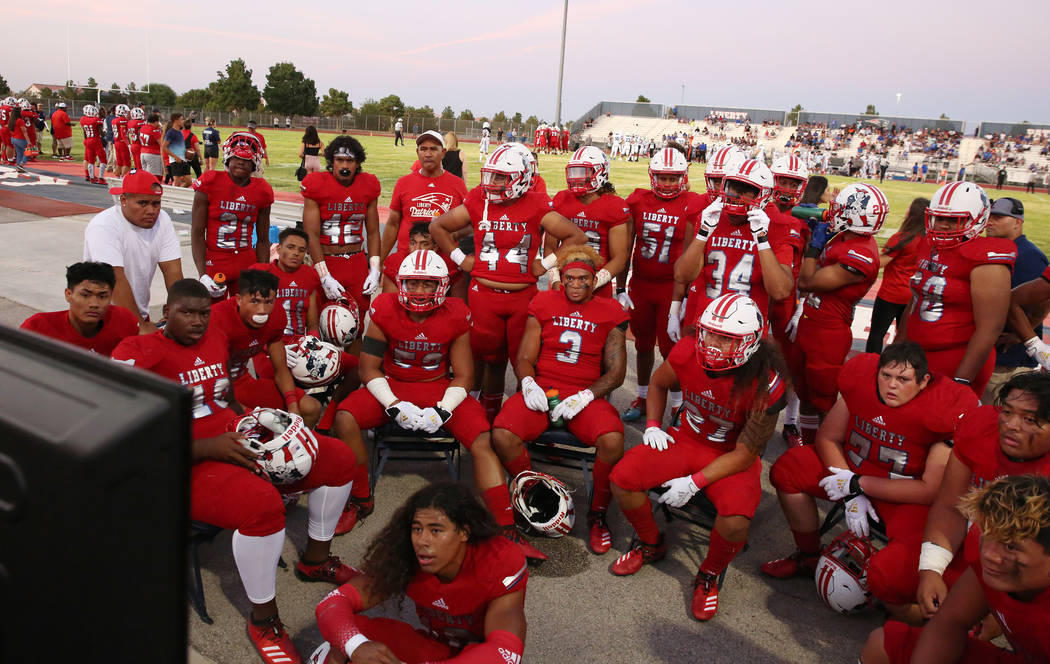 The Liberty High school football players review a play during a football game against Chandler, ...
