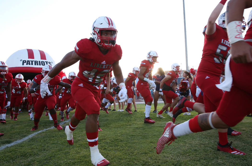The Liberty High school football players take the field during a football game against Chandler ...