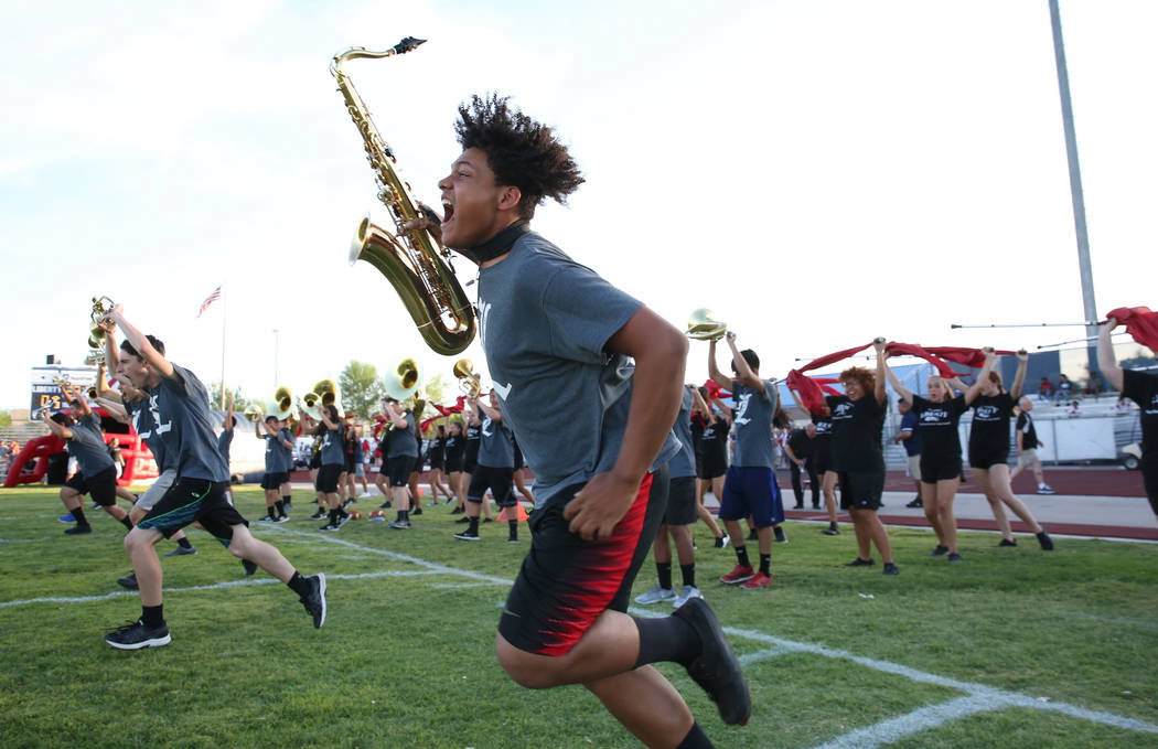 Member of the Liberty High marching band Damien Alexander, front, take the field during a footb ...