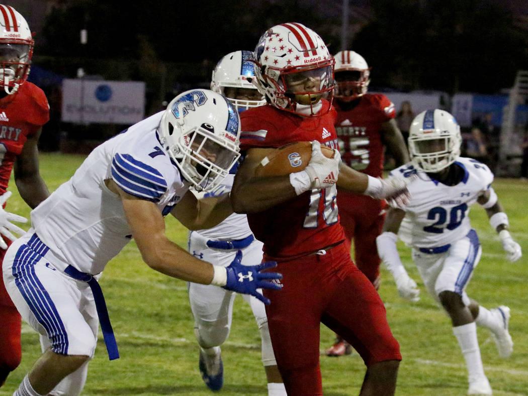 Liberty High's Maurice Hampton (16) tackled by Chandler, Ariz., High's Skyler Price (7) during ...