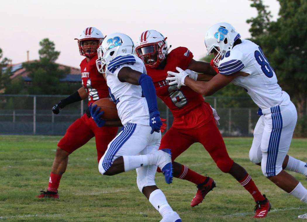 Chandler, Ariz., High's Quaron Adams (22) runs past Liberty High's Donte Bowers Jr. (6) during ...