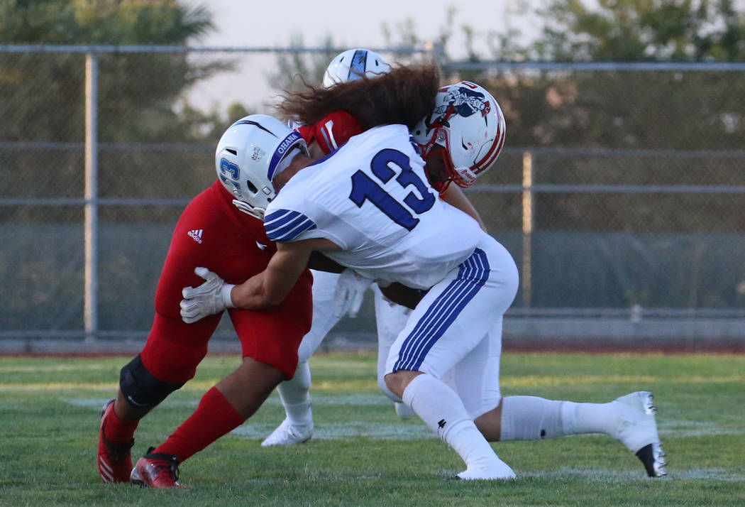 The Liberty High's Zyrus Fiaseu, left, protects the ball as he tackles Chandler, Ariz., High's ...