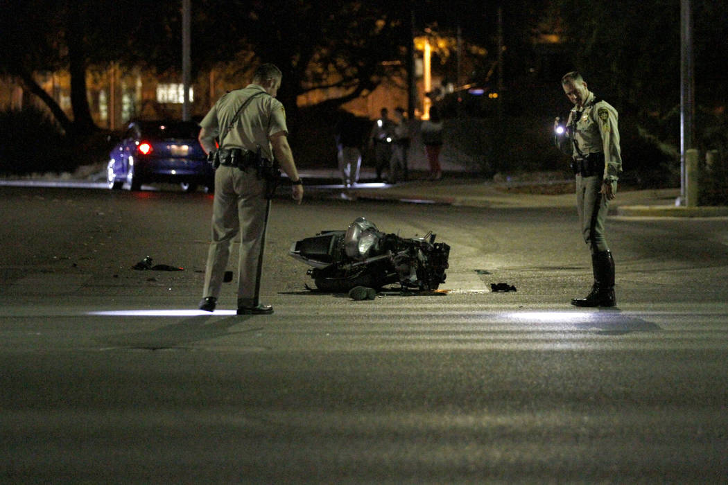 Las Vegas police officers investigate a fatal motorcycle crash at Martin Luther King Boulevard ...