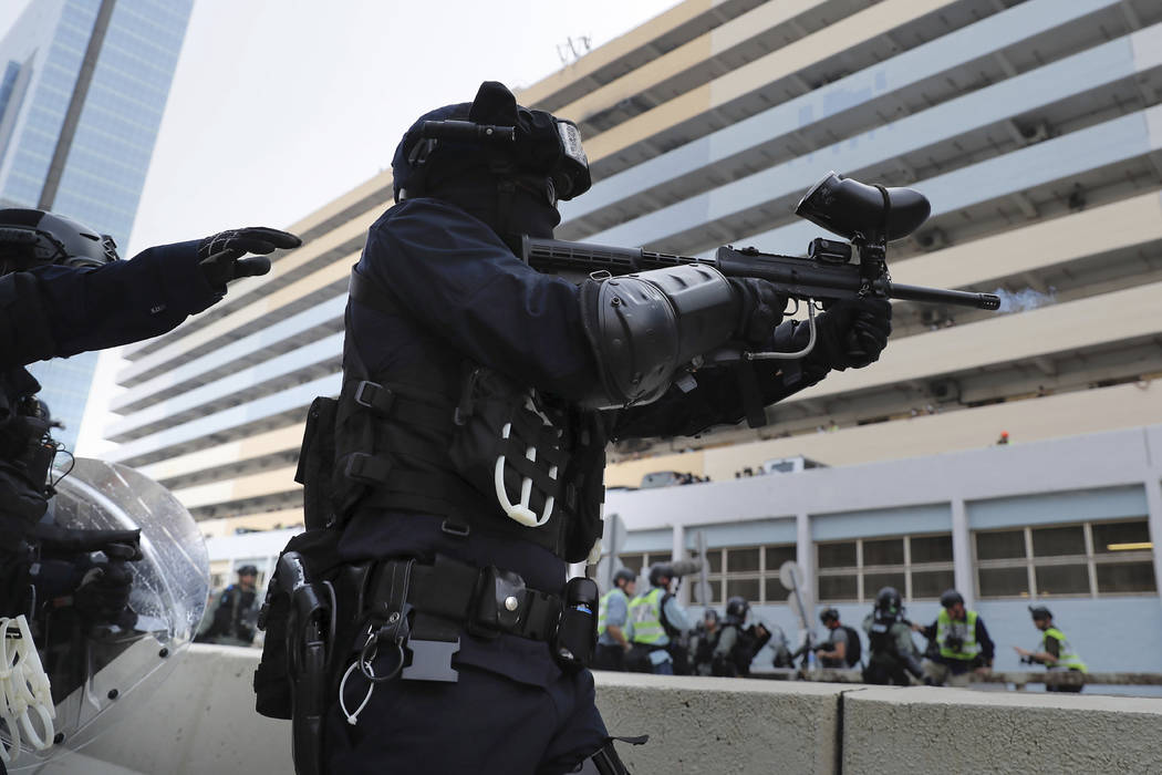 A police officer fires pepper balls during a demonstration in Hong Kong, Saturday, Aug. 24, 201 ...