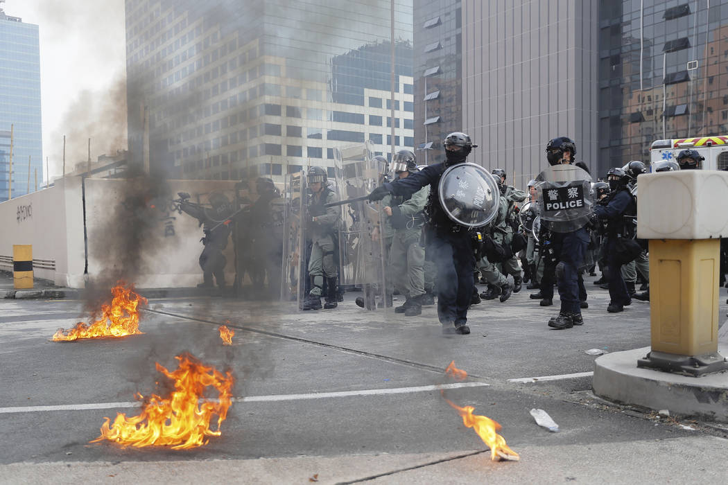 Riot police gather around small fires during a protest in Hong Kong, Saturday, Aug. 24, 2019. C ...