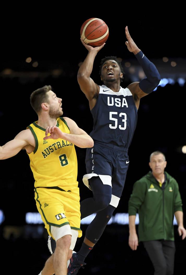 United States' Donovan Mitchell, right, attempts a basket against Australia's Matthew Dellavedo ...