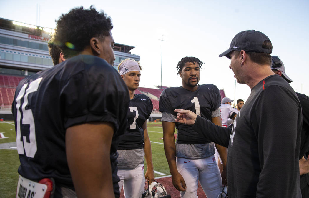 UNLV QB Armani Rogers (1, center) listens with others to quarterback's coach Ron O'Dell, right, ...