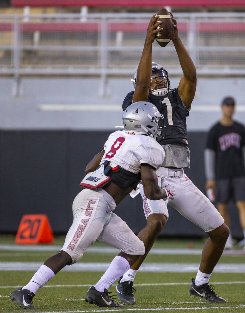 Quarterback Armani Rogers (1) reaches up to save a high snap during the UNLV football team scri ...