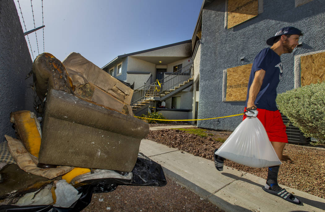 A neighbor passes by the burnt remains outside from an early morning fire at The Bristol at Sun ...