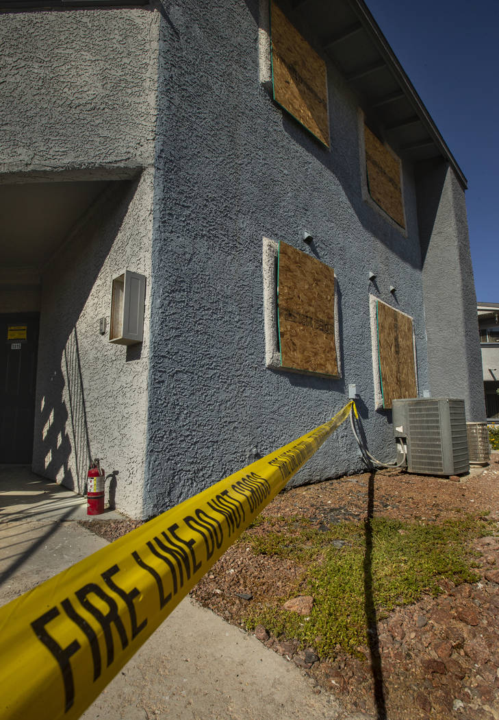Fire department warning tape blocks the apartment entrance from an early morning fire at The Br ...