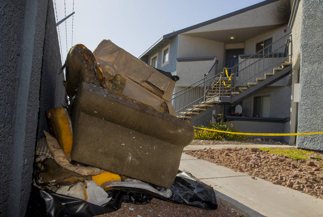 Remains stack up outside from an early morning fire at The Bristol at Sunset apartments in buil ...