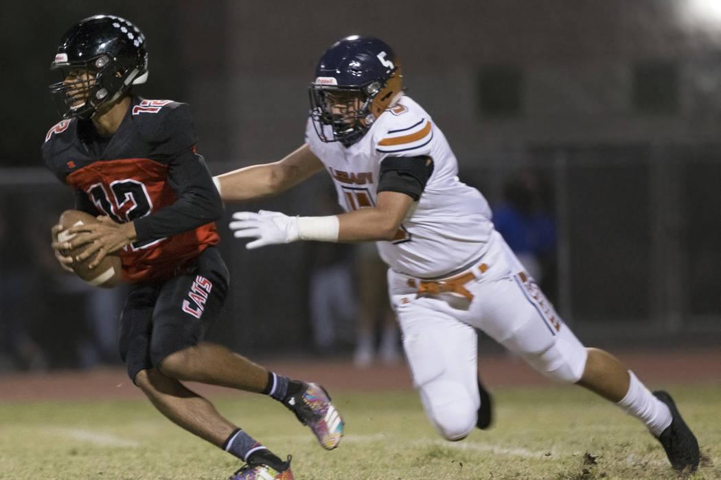 Las Vegas sophomore quarterback Ja'Shawn Scroggins (12) scrambles past Legacy junior linebacker ...