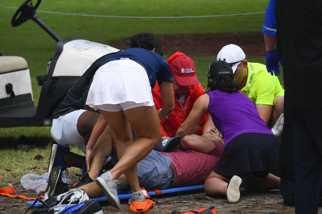 A spectators is tended to after a lightning strike on the course which left several injured dur ...