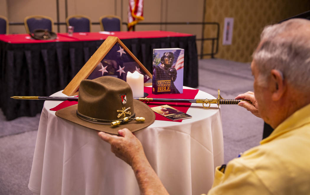 Pastor Bill Karabinos arranges a display as veterans and spouses who served in Vietnam particip ...