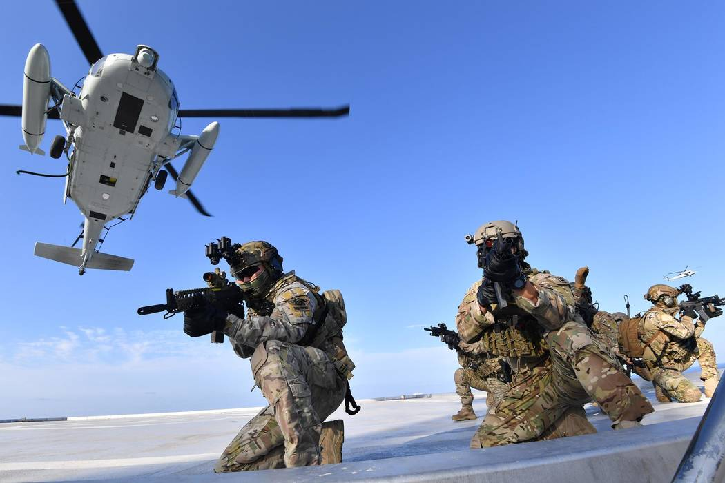 In this photo provided by South Korea's Navy, Members of South Korean Navy's special forces aim ...