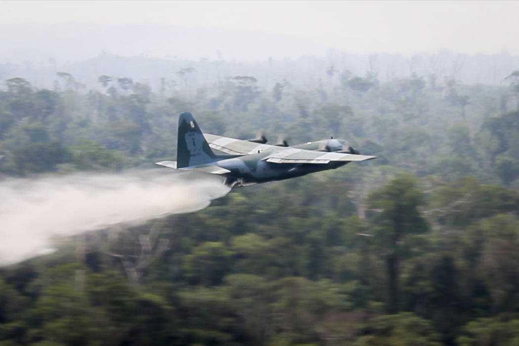 In this photo released by Brazil Ministry of Defense, a C-130 Hercules aircraft dumps water to ...