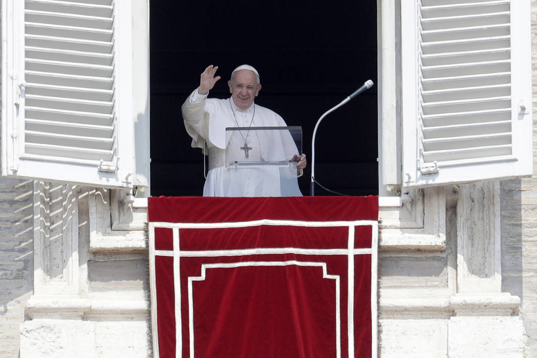 Pope Francis waves to faithful during the Angelus noon prayer in St. Peter's Square at the Vati ...