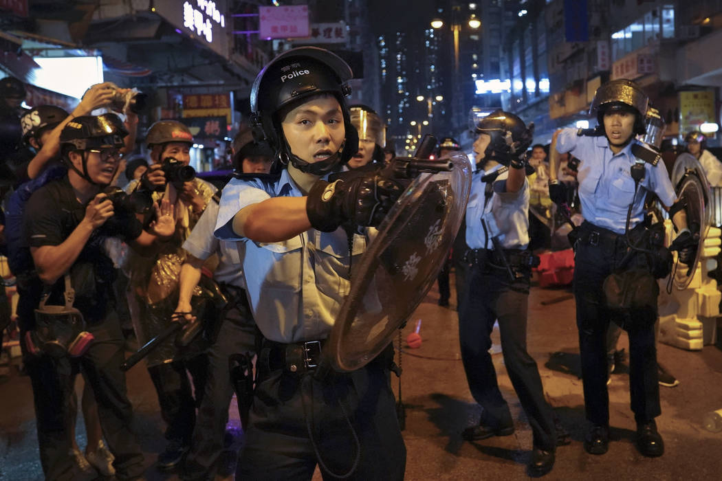 A policeman points his gun after confronting demonstrators during a protest in Hong Kong, Sunda ...