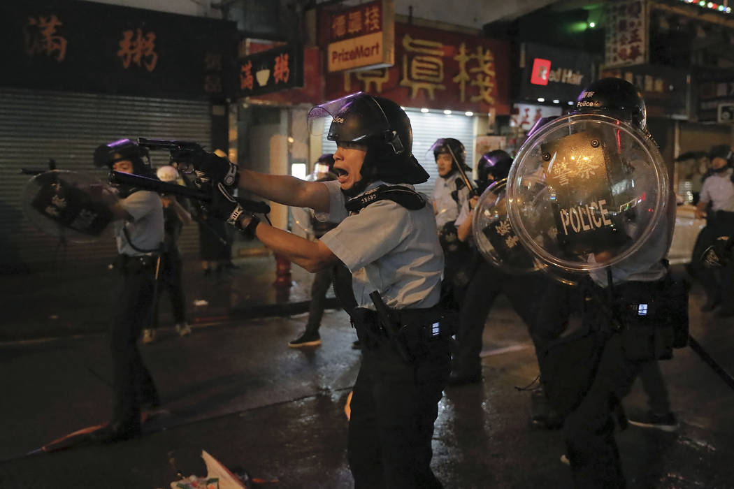 Policemen pull out their guns after a confrontation with demonstrators during a protest in Hong ...