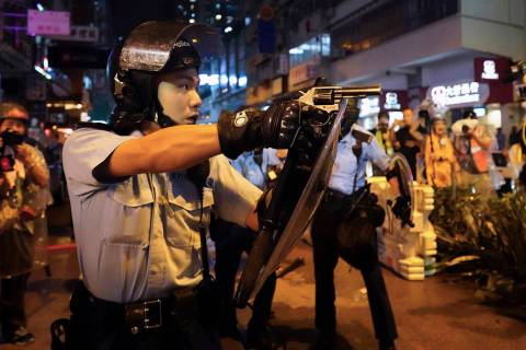A policeman points a weapon during a protest in Hong Kong, Sunday, Aug. 25, 2019. Hong Kong pol ...