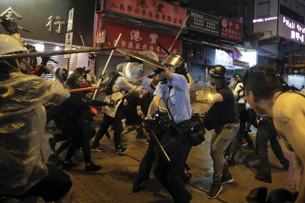 Policemen clash with demonstrators on a street during a protest in Hong Kong, Sunday, Aug. 25, ...