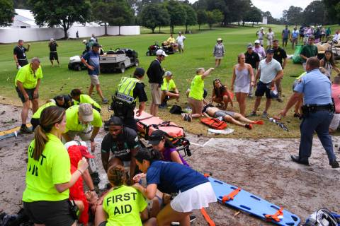 Spectators are tended to after a lightning strike on the East Lake Golf Club course left severa ...