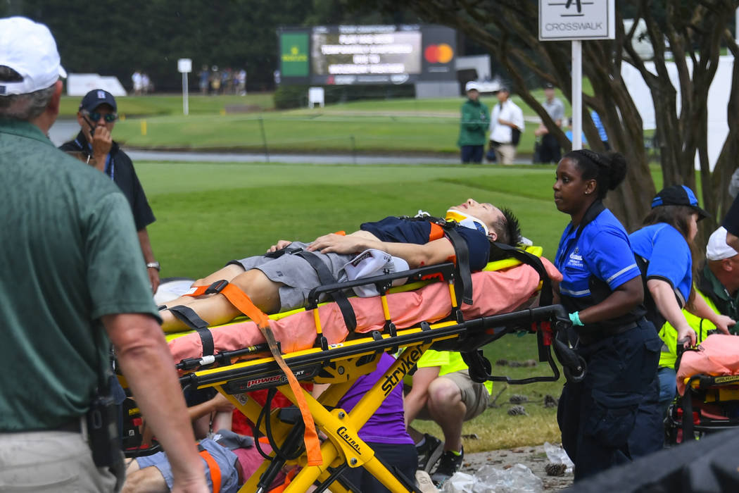 A spectator is taken to an ambulance after a lightning strike on the course which left several ...