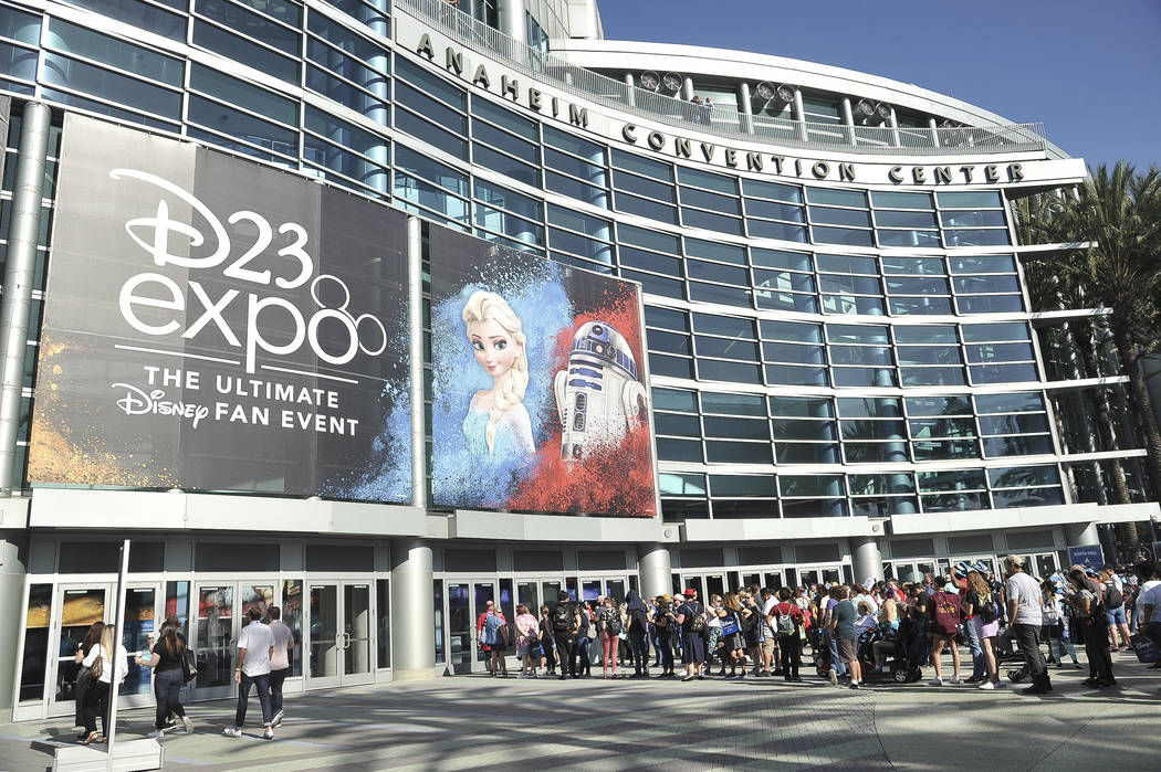 People line up in front of the Anaheim Convention Center during the 2019 D23 Expo on Saturday, ...
