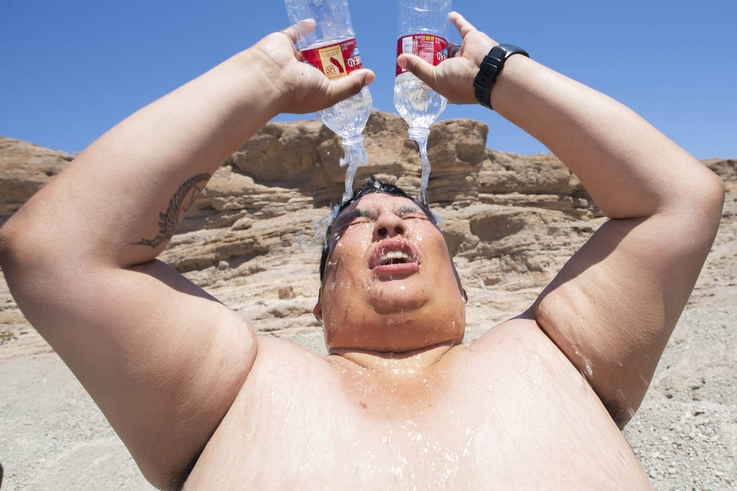 Omar Ramirez, 29, bathes with two water bottles during a hot summer day in the sun after pickin ...