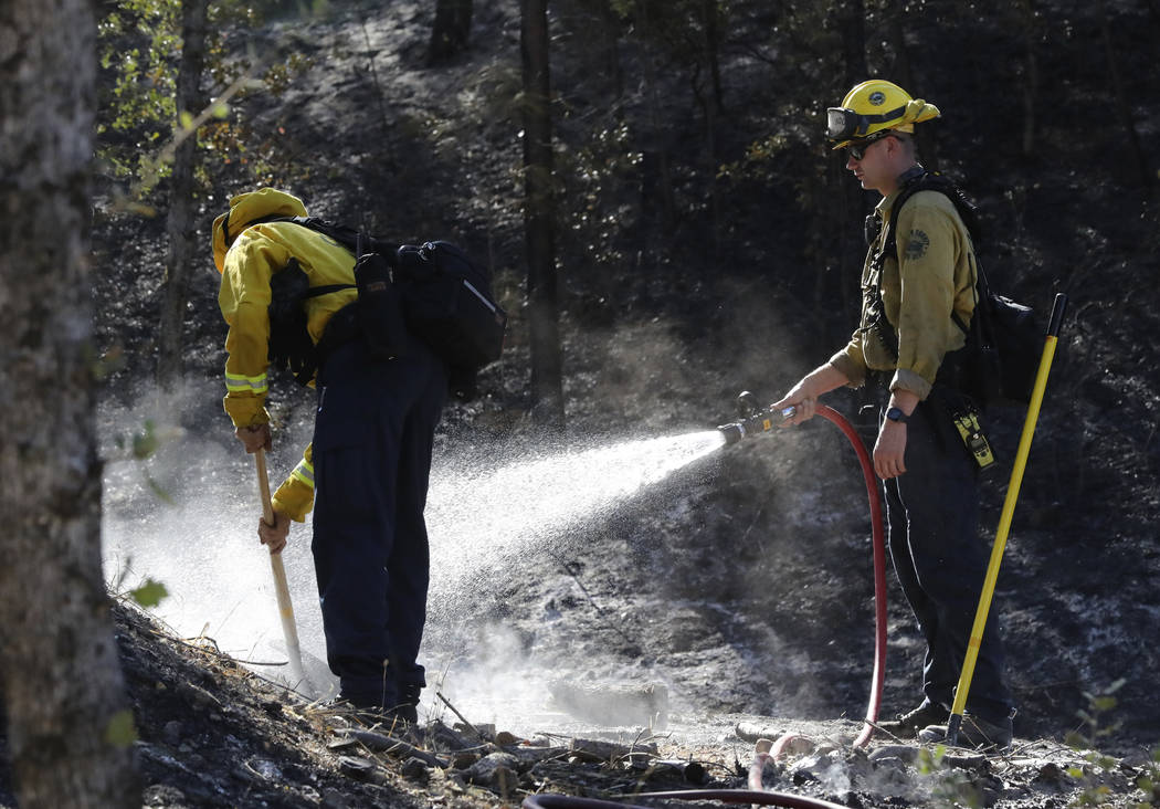 Firefighters from the Marin County Fire Department put out hot spots Friday, Aug. 23, 2019, a d ...