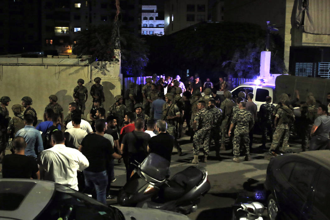 Lebanese security stand at the site where an Israeli drone was said to have crashed in a strong ...