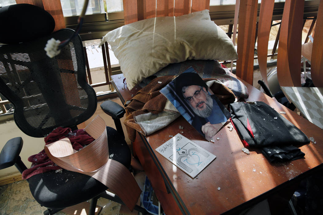 A poster of Hezbollah leader Sayyed Hassan Nasrallah is seen amid other damage inside the media ...