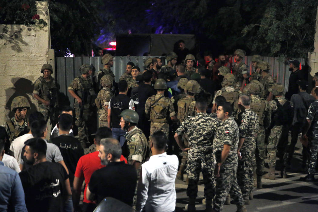Lebanese security stand near the site where an Israeli drone was said to have crashed in a stro ...