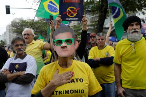 A woman wears a mask of Brazil's Justice Minister Sergio Moro during a rally in support of the ...