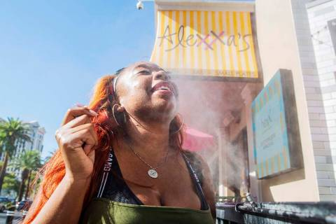 Shelle Ralph from North Carolina cools off from the heat in a water mist outside of Alexxa's Ba ...