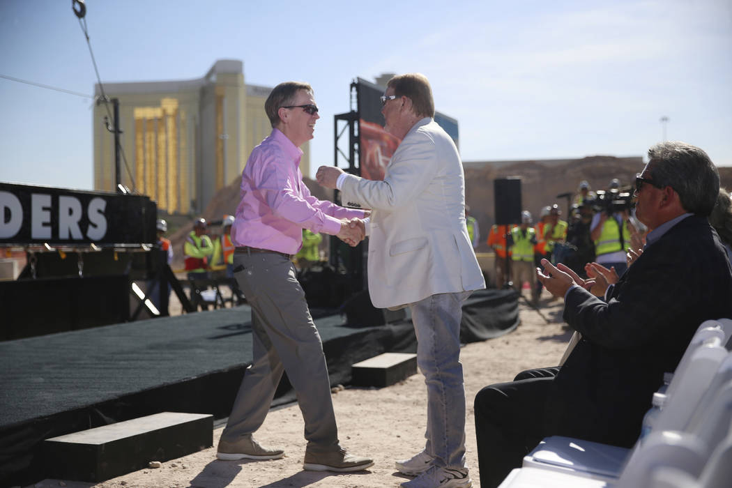 Allegiant Chairman and CEO Maury Gallagher, left, shakes hands with Raiders owner Mark Davis du ...