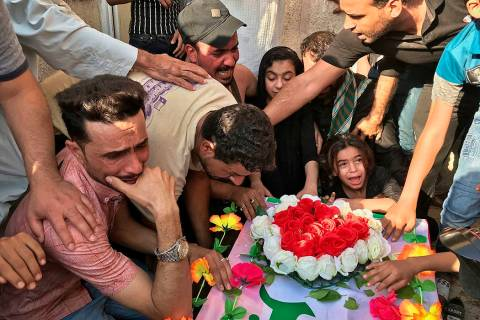 Mourners grieve at the coffin of Abu Ali al-Dabi, a fighter of the Popular Mobilization Forces ...