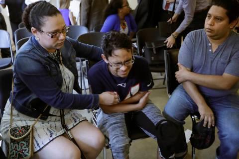 Gary Sanchez, of Honduras, right, watches as his wife, Mariela comforts their son, Jonathan, 16 ...