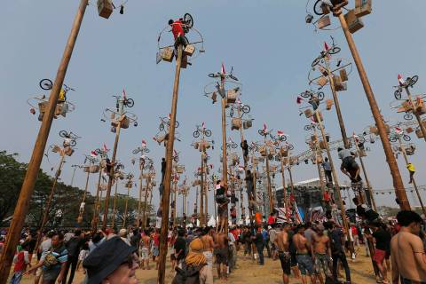 Participants struggle to reach the prizes during a greased-pole climbing competition held as pa ...