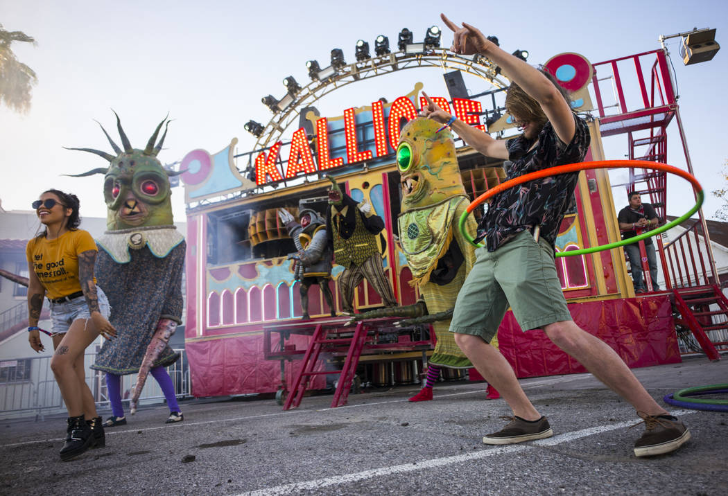 Creyton Bonestell of Palm Springs, Calif., right, hula hoops by the Kalliope art car during the ...