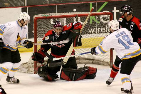 Las Vegas Wranglers goalie Mike McKenna, middle, makes the save in front of Phoenix Roadrunners ...