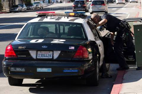 A Los Angeles Police Department officer talks to an occupant inside of his squad car. (Getty Im ...