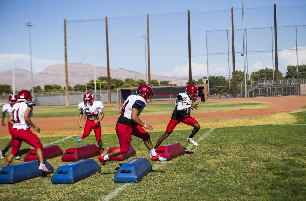 Players run through drills during football practice at the baseball field at Valley High School ...