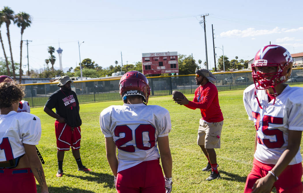 Valley coach Quincy Burts, second from right, leads football practice at the baseball field at ...