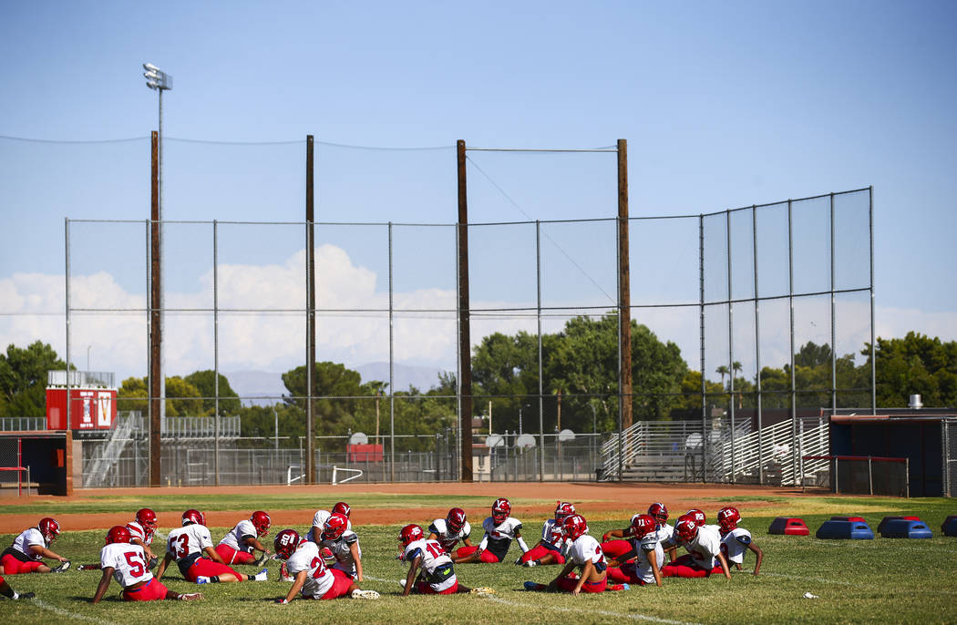Players stretch and warm up during football practice at the baseball field at Valley High Schoo ...