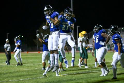 Desert Pines' Julian Lawence (21) celebrates with Malik Brooks (10) after scoring a touchdown a ...