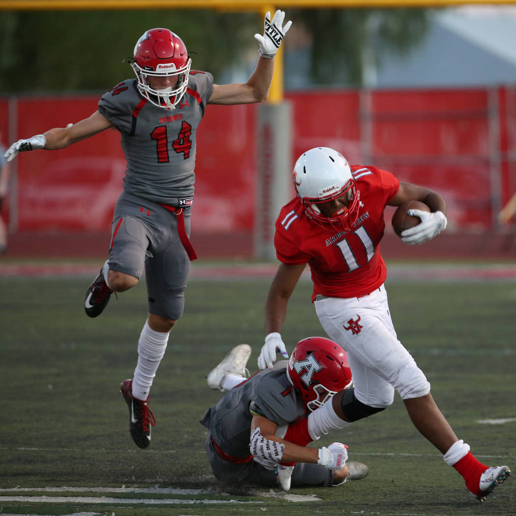 Arbor View's Jaedyn Jackson (11) runs the ball under pressure from American Fork's Fisher Inger ...