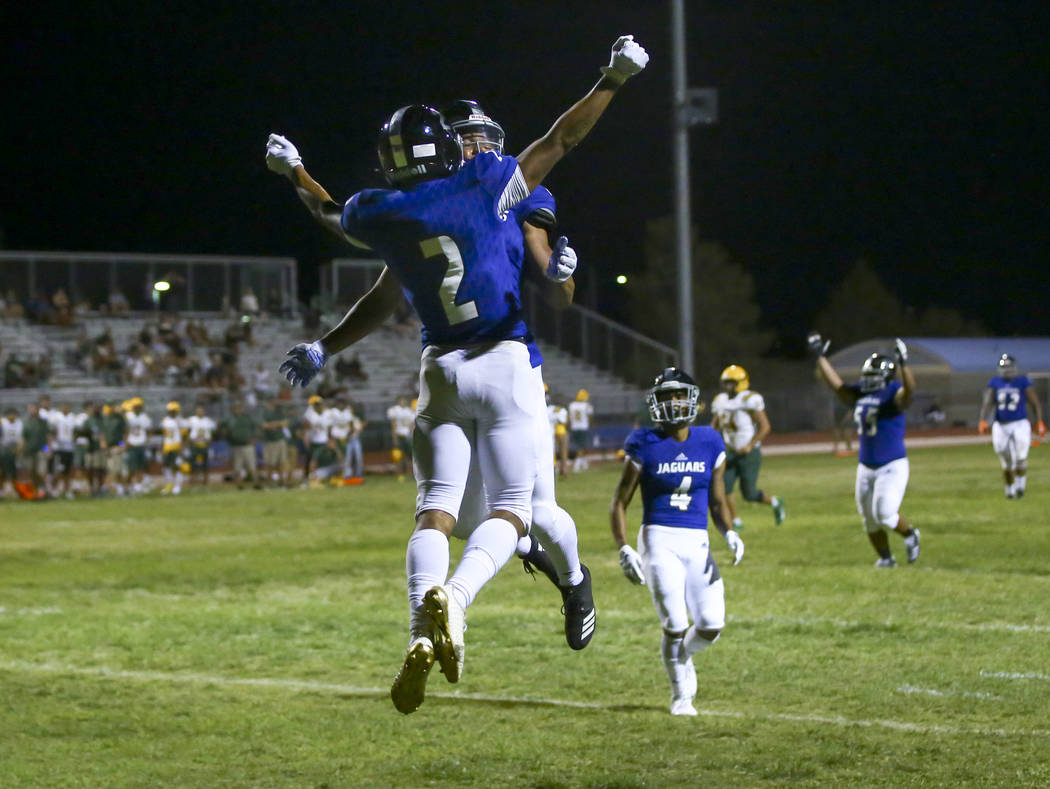 Desert Pines' Deandre Moore (2) celebrates his interception with Michael Jackson lll during the ...